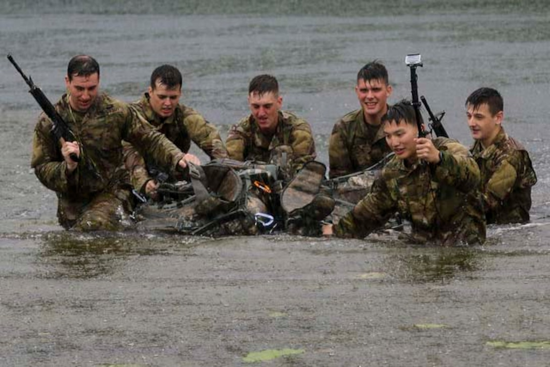 Six soldiers wade through water with a large debris in the middle.