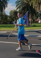 Erik Silva, a Special Olympics runner, holds a torch as he runs with U.S. Air Force 60th Security Forces Squadron defenders and athletes from Solano County during the Northern California Law Enforcement Torch Run June 20, 2019, at Travis Air Force Base, California. Hundreds of Law Enforcement personnel from northern California escorted the Special Olympics torch, the Flame of Hope, throughout their local communities in a relay to the 2019 Special Olympics Northern California Summer Games, being held at the University of California Davis campus June 21-23. (U.S. Air Force photo by Heide Couch)