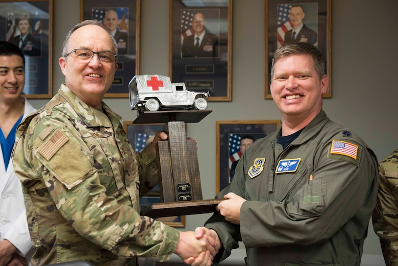 U.S. Air Force Maj. Gen. Lee Payne, Defense Health Agency assistant director, and Lt. Col. Daniel Hatcher, 92nd Aeromedical Squadron flight commander, pose with a commemorative trophy at the Fairchild Air Force Base clinic, Washington, April 26, 2019. Payne visited the medical group to check in on Airmen's progress in developing solutions to the continuous development with the new Medical Health System Genesis program. (U.S. Photo by Senior Airman Ryan Lackey)