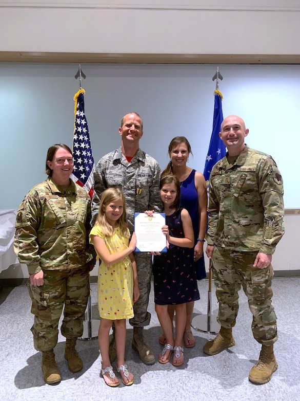 U.S. Air Force Col. Melissa Stone (far left), 363d ISR Wing commander, and Chief Master Sgt. Stefan Blazier (far right), 363d ISRW command chief, present Master Sgt. Zachary H. (center), 547th IS operations superintendent, with the Air Force Commendation Medal at Nellis Air Force Base, Nevada, June 14, 2019. Zachary led the renovation and modernization efforts to bring the U.S. Air Force's only threat training facility to meet the needs of today's warfighters from Nov. 1, 2018 to March 1, 2019.