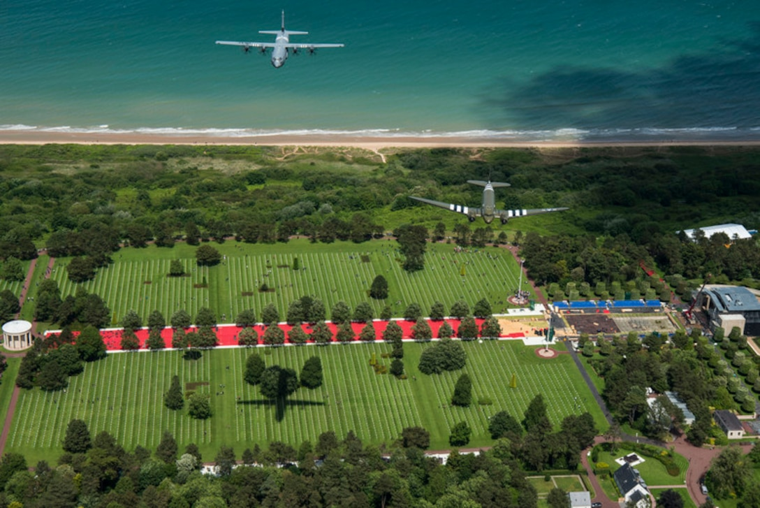 """A Douglas C-47 Dakota, nicknamed """"That's All Brother"""", flies with a U.S. Air Force C-130J Super Hercules, assigned to the 37th Airlift Squadron, Ramstein Air Base, Germany, over the Normandy American Cemetery and Memorial in Colleville-sur-Mer, France, June 8, 2019. """"That's All Brother"""" flew combat missions during Operation Neptune June 6, 1944. The 37th AS' lineage traces back to the 37th Troop Carrier Squadron, who flew C-47s with """"W7"""" or """"Whiskey 7"""" painted on the nose of their aircraft. The C-130J was painted in honor of the 37th TCS. (U.S. Air Force photo by Senior Airman Devin M. Rumbaugh)"""