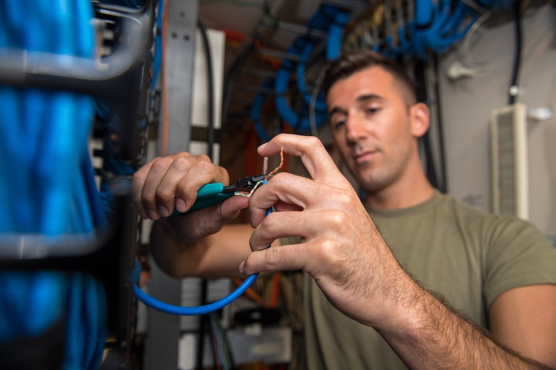 U.S. Air Force Tech. Sgt. Kenneth Overstreet, 178th Communications Squadron client systems from the Ohio Air National Guard, prepares a cable for connection at Tyndall Air Force Base, Florida, June 18, 2019.