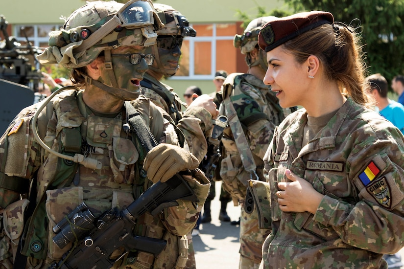 A U.S. soldier carrying a rifle and wearing a uniform and camouflage face paint talks to a Romanian soldier.