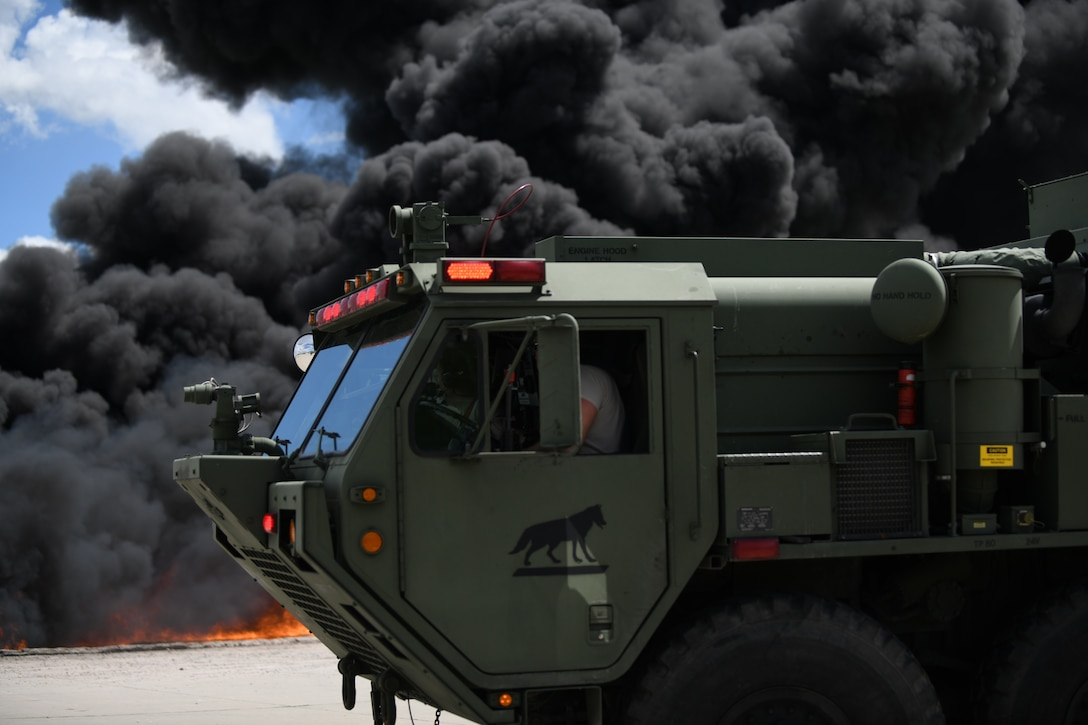 A firetruck from South Dakota's National Guard prepares to extinguish a mock aircraft fire at Ellsworth Air Force Base, S.D., June 12, 2019. For larger fires, fire trucks drive around the fire pit and use turrets connected to the fire truck to extinguish the flames. (U.S. Air Force photo by Airman 1st Class Christina Bennett)