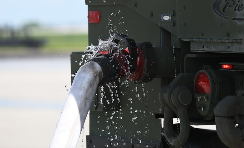 Firetrucks from South Dakota's National Guard are filled with water prior to a modulation training exercise at the fire pit on Ellsworth Air Force Base, S.D., June 12, 2019. The firetrucks can hold approximately 1,000 gallons of water. During the course of two days, 8,000 to 10,000 gallons of water were used during the fire trainings. (U.S. Air Force photo by Airman 1st Class Christina Bennett)