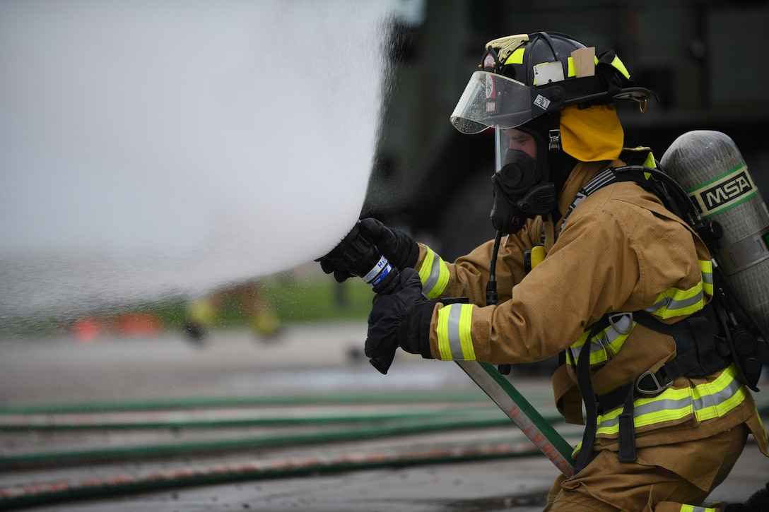 A firefighter from Nebraska's Army National Guard performs a nozzle stream check, prior to participating in a handline fire training exercise at the fire pit on Ellsworth Air Force Base, S.D., June 13, 2019. Before training, firefighters must examine all of their equipment to ensure that everything works properly and to reduce the chance of safety incidents. (U.S. Air Force photos by Airman 1st Class Christina Bennett)