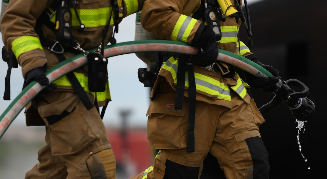 Nebraska Army National Guard firefighters extinguished a handline fire during a qualification training exercise at Ellsworth Air Force Base, S.D., June 13, 2019. Firefighters douse the handline fire with water, by moving around the fire pit on foot and using a hose that connects to the fire truck.  The flames from fuel fires tend to move whereas propane fires don't, this provides fireman with a realistic training experience. (U.S. Air Force photo by Airman 1st Class Christina Bennett)
