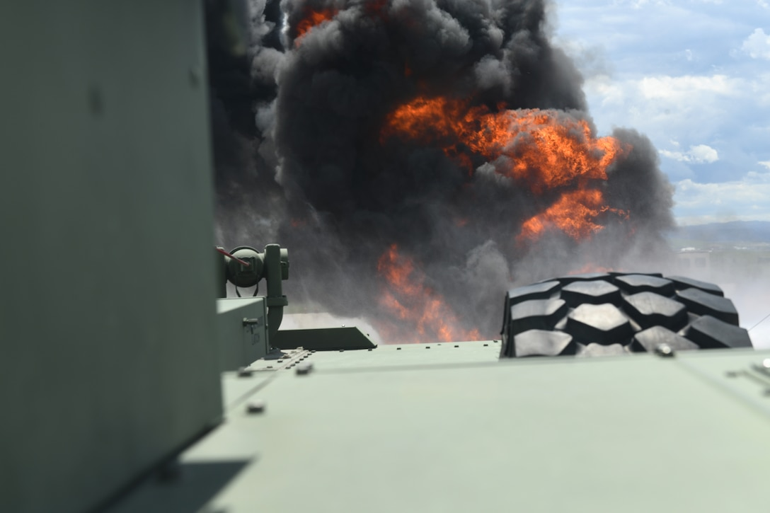 Flames can be seen from the inside of a firetruck during a modulation fire training exercise at Ellsworth Air Force Base, S.D., June 12, 2019. At the pit, modulation trainings use anywhere between 300 and 500 gallons of jet fuel. (U.S. Air Force photo by Airman 1st Class Christina Bennett)