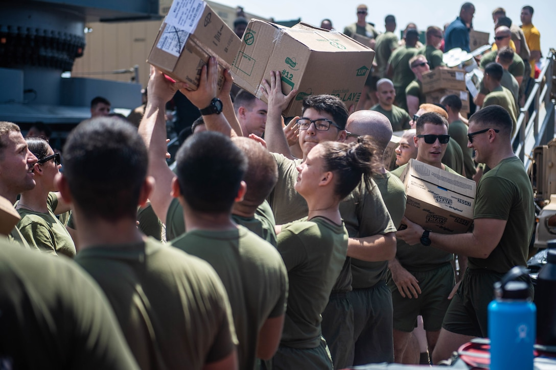 Sailors and Marines line up and pass boxes of supplies to one another aboard a ship.