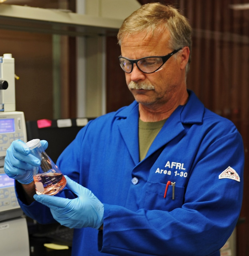 Milton McKay, a research chemist from the Air Force Research Laboratory's Rocket Propulsion Division at Edwards AFB, California, examines a sample of the AFRL developed ASCENT (Advanced Spacecraft Energetic Non-toxic Propellant) green propellant. (Courtesy photo)