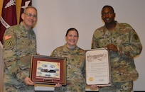 Brig. Gen. George Appenzeller (left), Brooke Army Medical Center commanding general, and Sgt. Maj. James Brown (right), chief clinical noncommissioned officer, present Army Capt. Ellen Simpson with the San Antonio Pride Month proclamation and a token of appreciation June 19 during the BAMC Pride Month observance. Simpson is a perioperative registered nurse at BAMC.