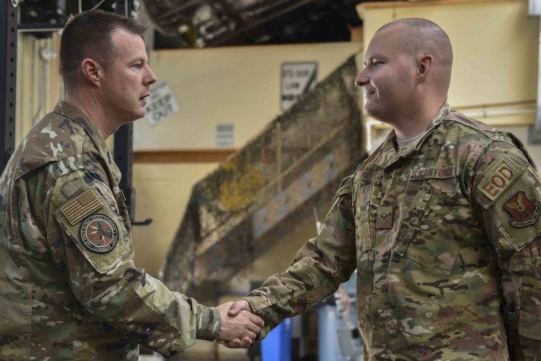 U.S. Air Force Chief Master Sgt. Charles Hoffman, Air Force Global Strike Command command chief, coins Senior Airman Norman Parks, 377th Mission Support Group Explosive Ordinance Disposal technician at Kirtland Air Force Base, June 13, 2019. Hoffman visited with Airmen across the 377th Air Base Wing to learn more about them and their mission. (U.S. Air Force photo by Airman 1st Class Austin J. Prisbrey)
