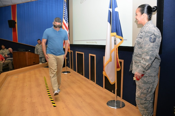 Jose Castro, 433rd Airlift Wing Financial Management Office budget technician, attempts to walk a straight line while wearing special goggles that simulate being intoxicated, as Master Sgt. Stephanie O. Sanchez, 433rd AW occupational safety manager, briefs Reserve Citizen Airmen about driving while intoxicated prevention at a wing civilian call June 20, 2019 at Joint Base San Antonio-Lackland, Texas.