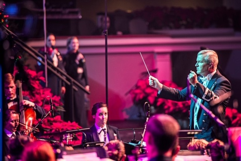 """Oboist Tech. Sgt. Emily Foster watches Col. Larry Lang as he conducts The U.S. Air Force Concert Band in a performance at DAR Constitution Hall. The concert was part of the Band's """"Spirit of the Season"""" holiday shows in Washington, D.C."""