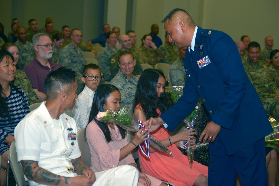 U.S. Air Force Lt. Col. Elbert G. Mose, incoming 81st TRSS commander, hands out flowers to his family members during the 81st TRSS change of command ceremony in the Roberts Consolidated Aircraft Maintenance Facility on Keesler Air Force Base, Mississippi, June 20, 2019. Mose assumed command from Lt. Col. Stephen P. Arnott with the passing of the guidon. The passing of the guidon is a ceremonial symbol of exchanging command from one commander to another. (U.S. Air Force photo by Airman Seth Haddix)