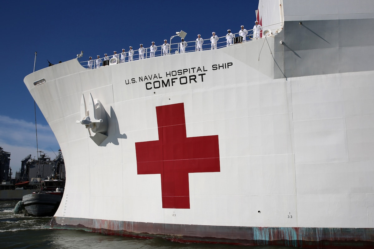 Sailors man the rails as the USNS Comfort pulls away from pier.