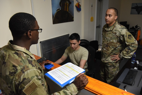 Senior Airman David Gonzalez (center) and Staff Sgt. Alberto Barreto (right), both 380th Air Expeditionary Wing  finance customer service representatives, assist an Airman with in-processing June 6, 2019, at Al Dhafra Air Base, United Arab Emirates.