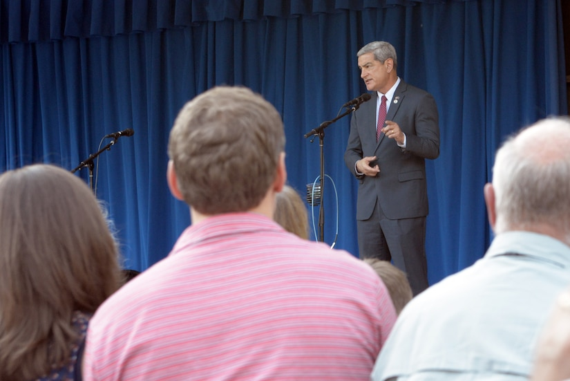 A man speaks from behind a microphone. In the background is a blue curtain. In the foreground are the backs of the heads of the audience.