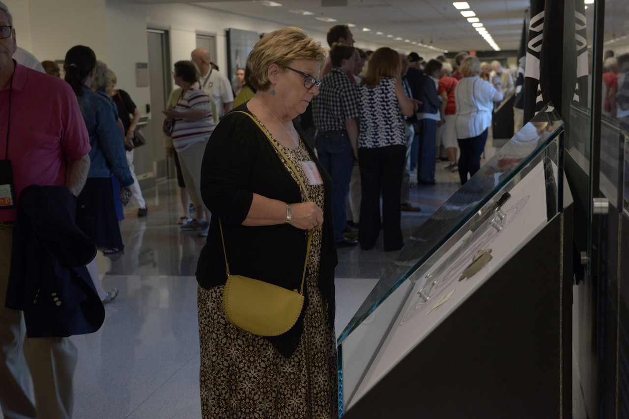 A woman looks at a museum-like exhibit in a large hallway.