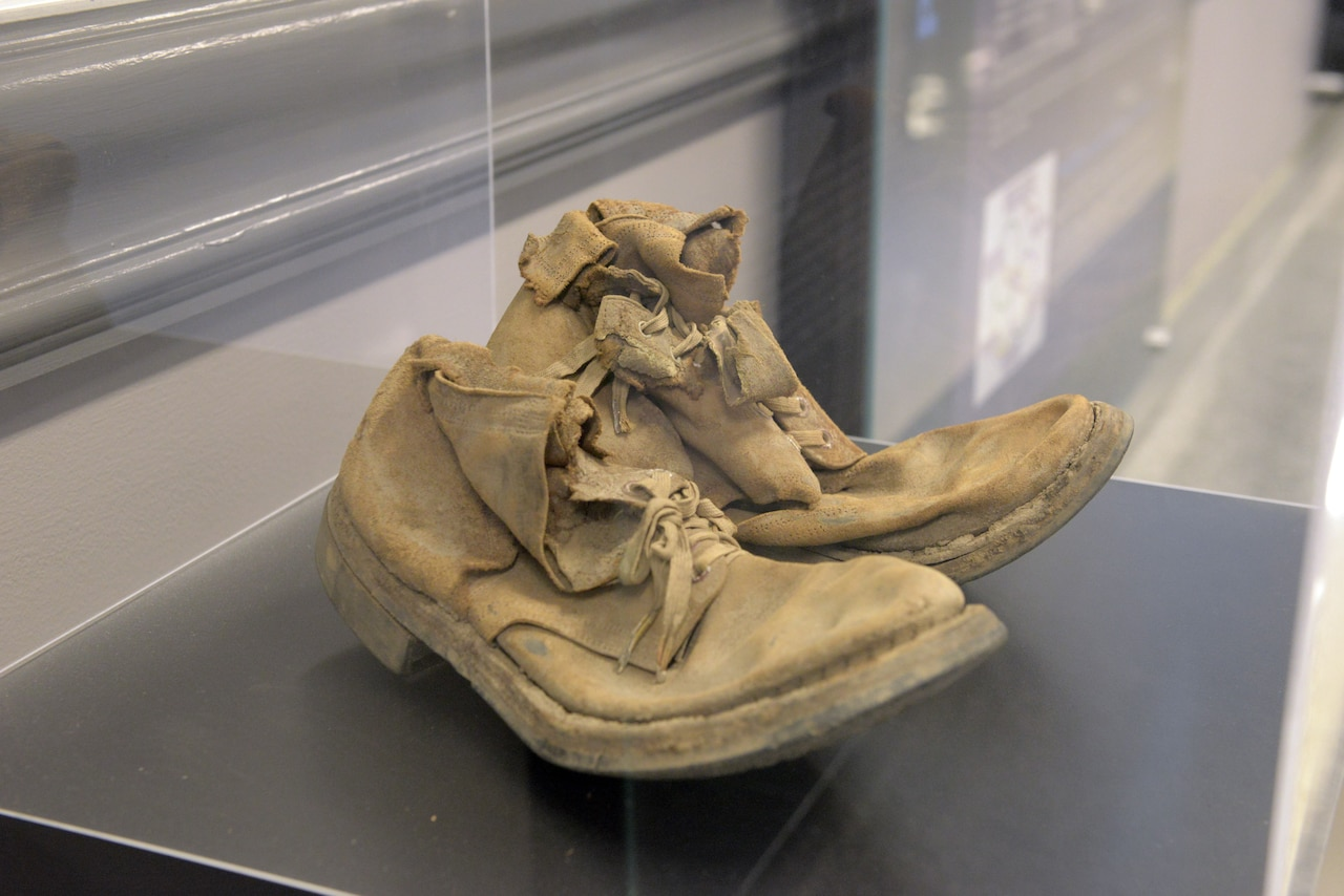A pair of beige combat boots sits inside a clear plastic display case.