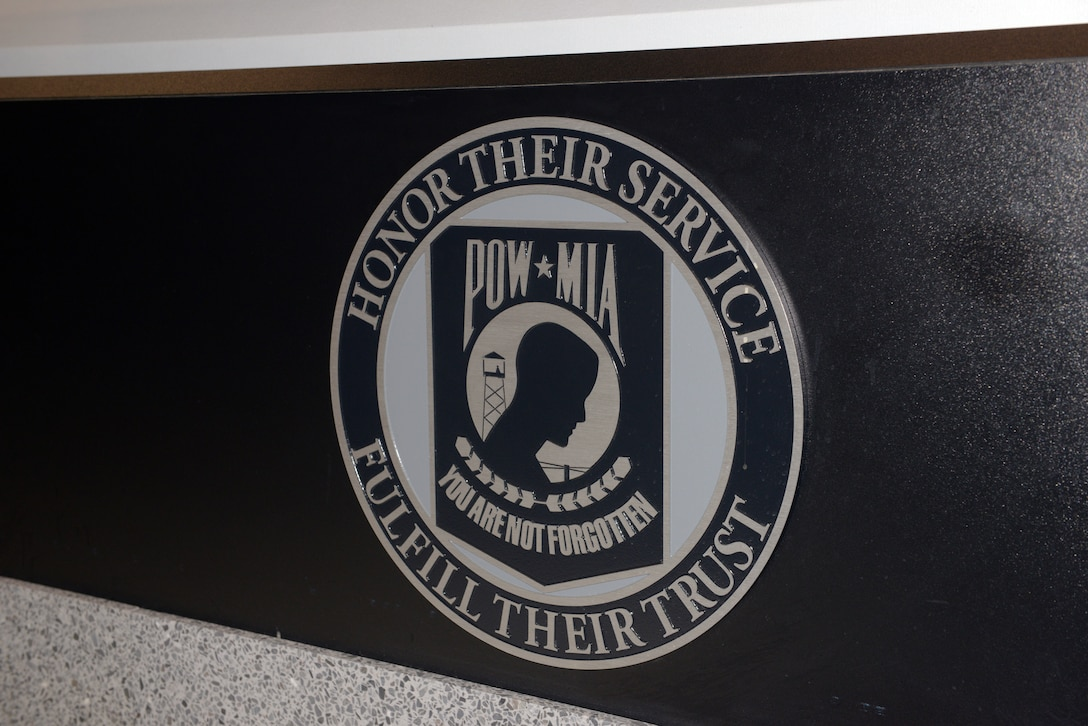 "A circular logo bears the words ""Honor Their Service —  Fulfill Their Trust"" and ""POW/MIA — You Are Not Forgotten."""