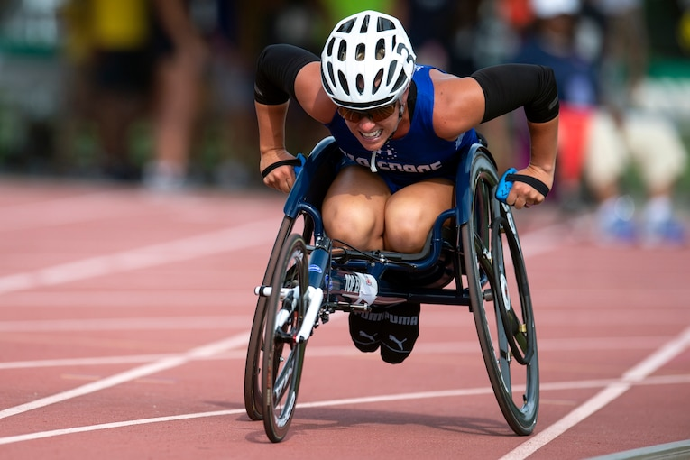 A veteran in a wheelchair races on a track.