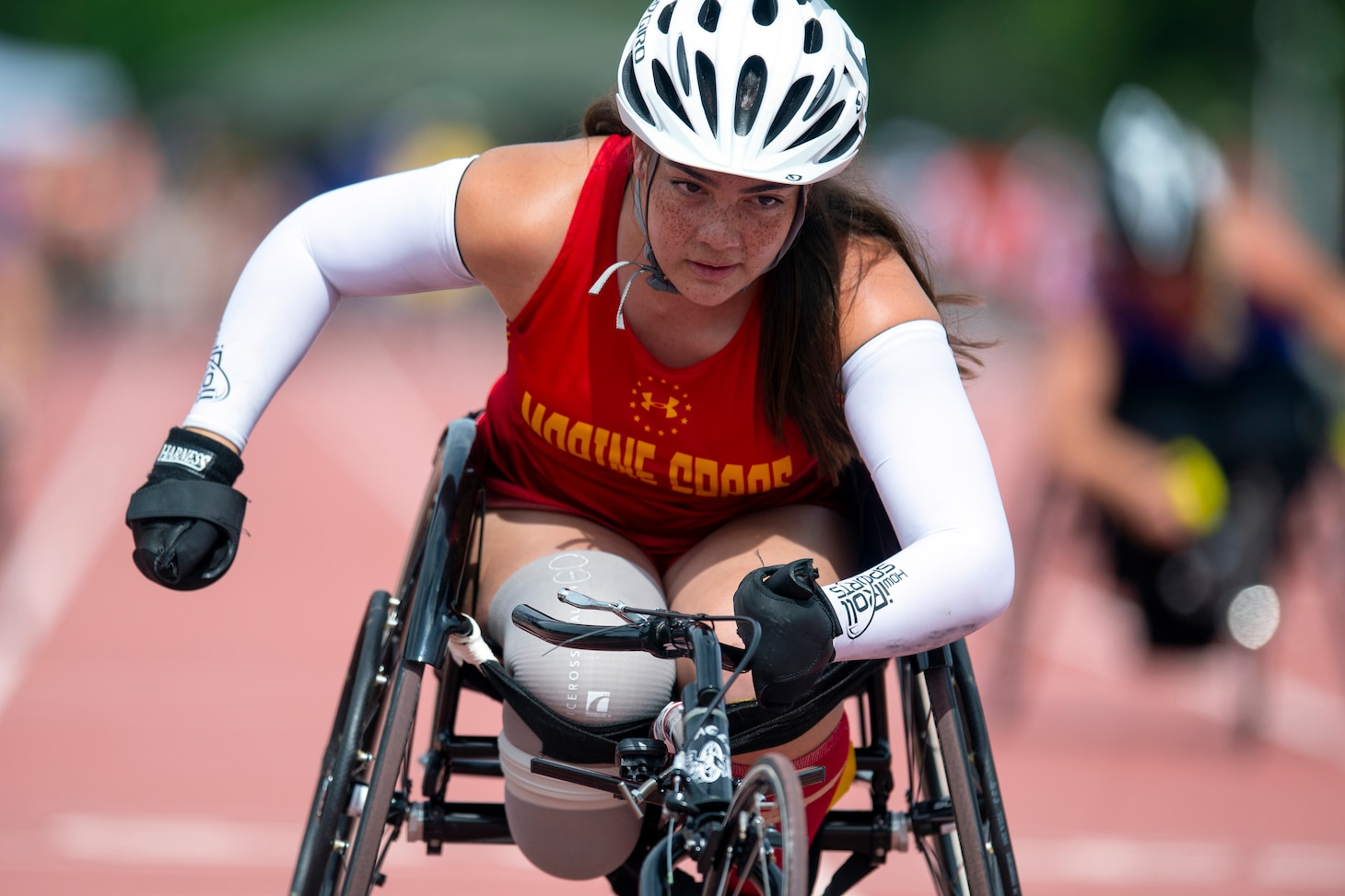 A female wheelchair racers drives towards the finish line during the 2019 Warrior Games.