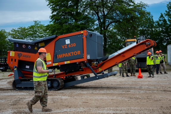 U.S. Army Staff Sgt. Donald Day guides a shredder into position
