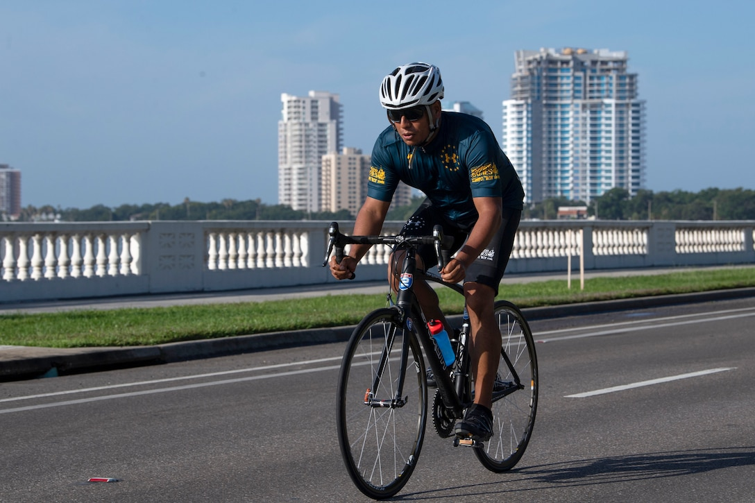 A Navy athlete rides a bike on a city street with highi-rise buildings in the background.