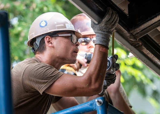 U.S. Navy Steelworker Constructionman Joseph Synowiec, assigned to Naval Mobile Construction Battalion (NMCB) 4, uses a tape measure to determine where members of the Royal Thai Armed Forces will place a gutter at the Ban Surasak School project site during Pacific Partnership 2019. (Mass Communication Specialist 2nd Class Kelsey L. Adams)