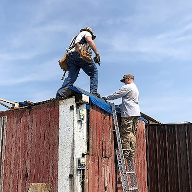 655th Intelligence, Surveillance, and Reconnaissance Wing, 71st Intelligence Squadron, Director of Operations Maj. Miller (first name withheld) and another volunteer repair a structure at a Dayton area farm June 1, 2019. Several tornados caused several injuries and severe property damage earlier in the week.