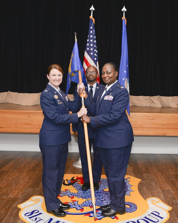 U.S. Air Force Col. Beatrice Dolihite, 81st Medical Group commander, gives the 81st Inpatient Operations Squadron guidon to Col. Mary Parker, incoming 81st IPTS commander, during the 81st IPTS change of command ceremony inside the Don Wylie Auditorium on Keesler Air Force Base, Mississippi, June 21, 2019.