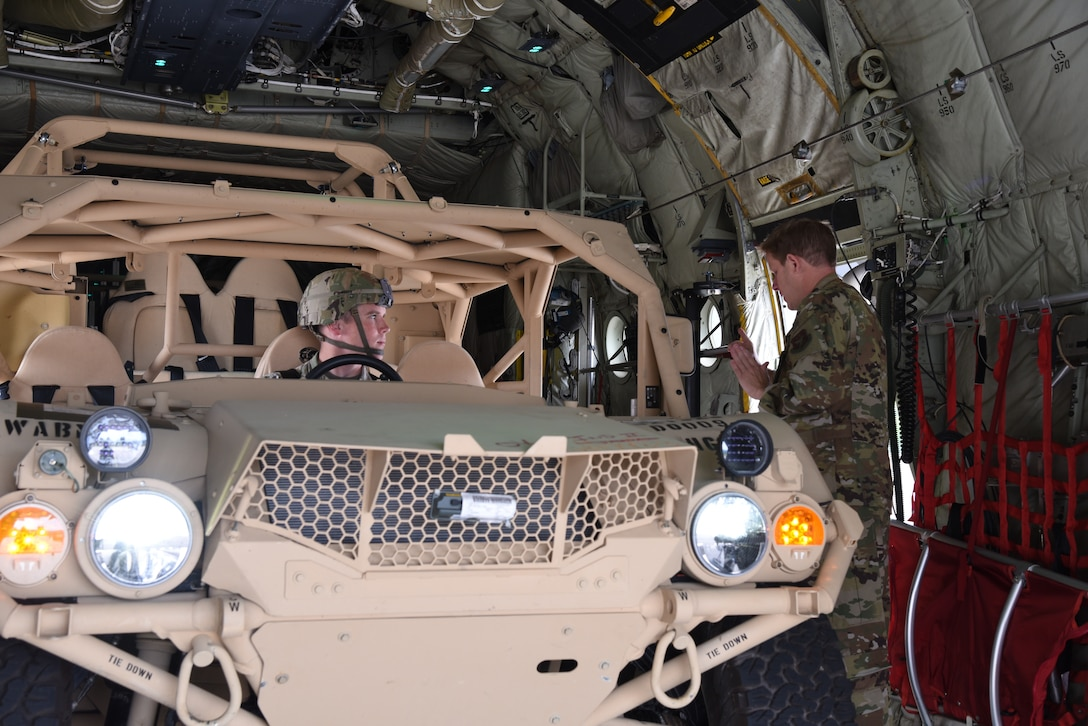 Senior Master Sgt. Eric Gassiot, a loadmaster with the 815th Airlift Squadron, 403rd Wing, explains the procedures for vehicle operations to Corporal Jared Guden, 82nd Airborne, scout platoon team leader, after he drove a ground mobility vehicle onto a C-130J in preparation for exercise Swift Response 19, June 14, 2019. The exercise is one of the premier military crisis response training events featuring high readiness airborne forces from eight NATO nations. Activities include intermediate staging base operations, multiple airborne operations, and several air assault operations. The Swift Response exercises have had great success in creating a foundation for the strong relationships we share with several European allies and partners today. (U.S. Air Force photo by Master Sgt. Jessica Kendziorek)