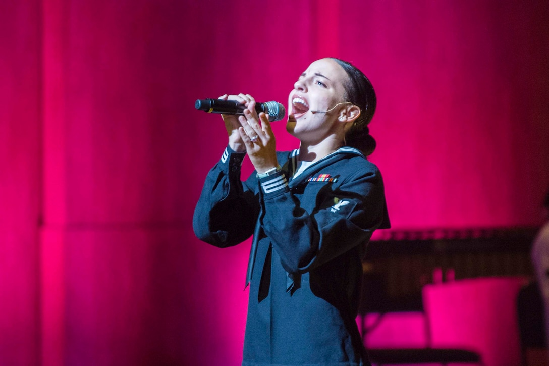A sailor sings into a microphone in front of a pink wall.