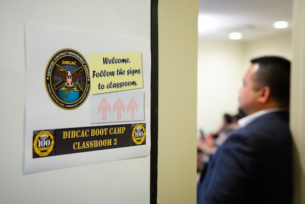 A man stands near a door, the door has a sign that says Welcome, follow the signs to the classroom. DIBCAC Boot Camp.