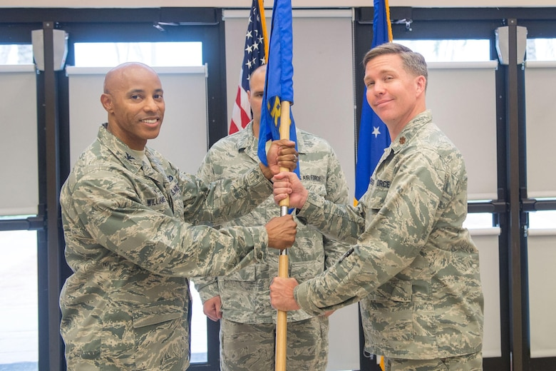 Col. Kevin Williams, 45th Mission Support Group commander, presents Maj. Christopher Jacobson, incoming 45th Logistics Readiness Squadron commander, with the 45th LRS guidon as he assumes command of the squadron, June 13, 2019, at Patrick Air Force Base, Fla. (U.S. Air Force photo by Derwin Oviedo)
