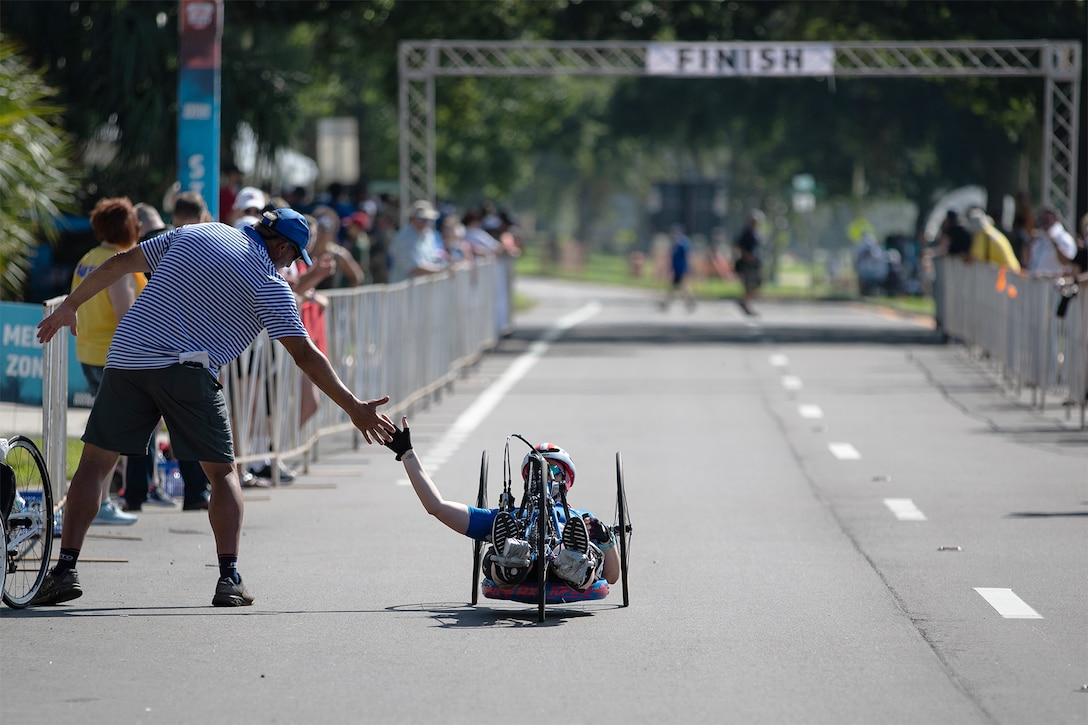 A service member high-fives a coach after crossing the finish line in a hand cycling event.