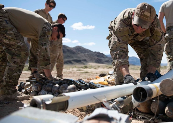 Explosive Ordnance Disposal technicians lay unexploded ordnance on the ground.