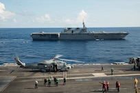 (June 19, 2019) Japan Maritime Self-Defense Force (JMSDF) ship JS Izumo (DDH-183) sails alongside the Navy™s forward-deployed aircraft carrier USS Ronald Reagan (CVN 76) while an MH-60R Sea Hawk from Helicopter Maritime Strike Squadron (HSM) 77 conducts flight operations. Ronald Reagan, the flagship of Carrier Strike Group 5, provides a combat-ready force that protects and defends the collective maritime interests of its allies and partners in the Indo-Pacific region.
