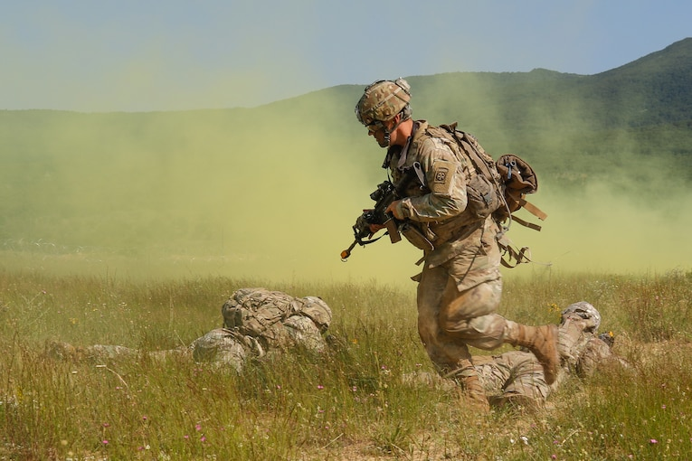 A soldier wearing a combat uniform and carrying a rifle runs behind two other soldiers lying in a field providing cover as smoke spreads.