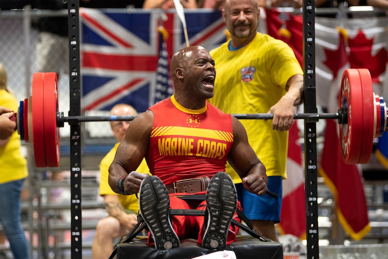 A Marine flexes after a successful bench press.