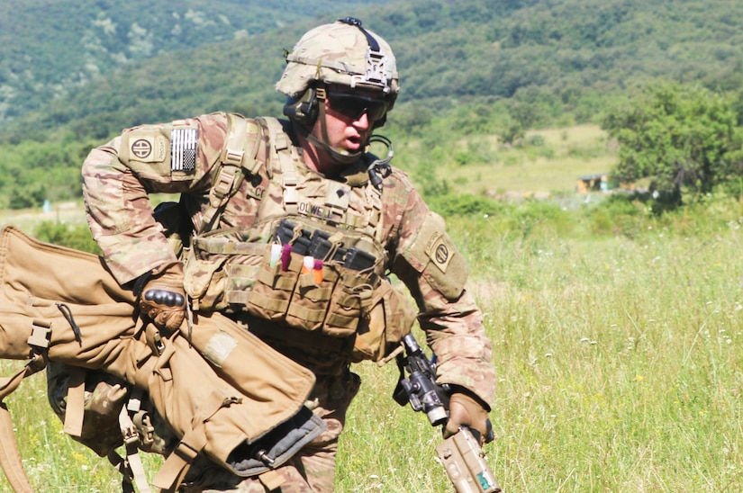 A soldier in combat gear moves quickly while carrying a rifle, a backpack and an extra weapon bag.