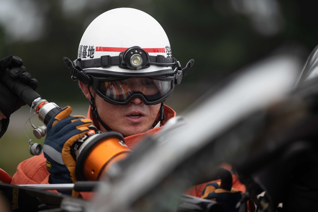 Japan Air Self Defense Force member Nishi Yoichi applies a hydraulic rescue tool known as the Jaws of Life while training with Airmen assigned to the 18th Civil Engineer Squadron fire and emergency services flight, as part of a bilateral exchange at Kadena Air Base, Japan, June 19, 2019.