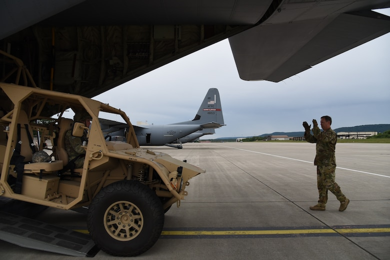 Senior Master Sgt. Dave Cooper, a loadmaster with the 815th Airlift Squadron, 403rd Wing, directs Corporal Jared Guden, 82nd Airborne, scout platoon team leader, as he drove a ground mobility vehicle, onto a C-130J in preparation for exercise Swift Response 19, June 14, 2019. The exercise is one of the premier military crisis response training events featuring high readiness airborne forces from eight NATO nations. Activities include intermediate staging base operations, multiple airborne operations, and several air assault operations. The Swift Response exercises have had great success in creating a foundation for the strong relationships we share with several European allies and partners today. (U.S. Air Force photo by Master Sgt. Jessica Kendziorek)