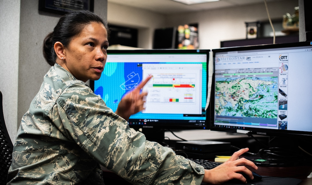 U.S. Air Force Capt. Richelle Greer, 18th Operations Support Squadron weather flight commander, monitors tropical cyclone conditions of readiness.