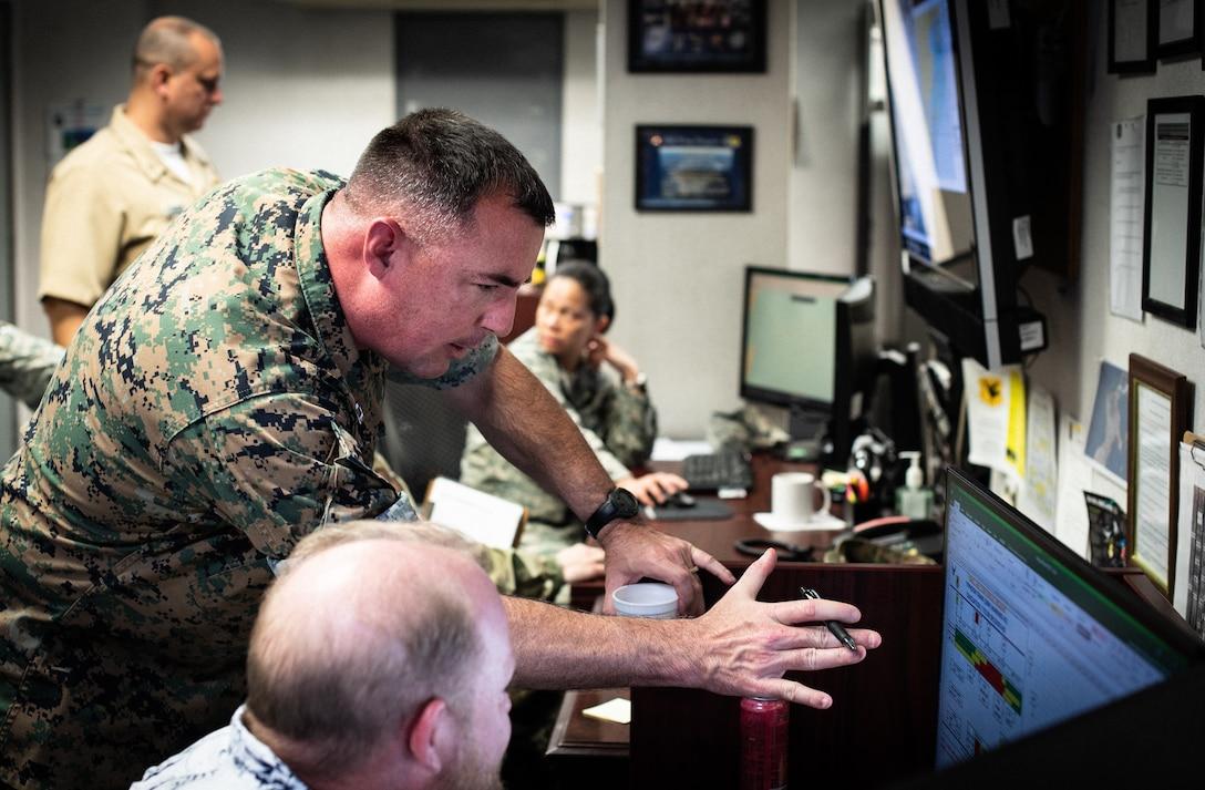 U.S. Marine Corps Capt. George Mills, senior weather officer, III Marine Expeditionary Force Weather, works alongside sister-service members.