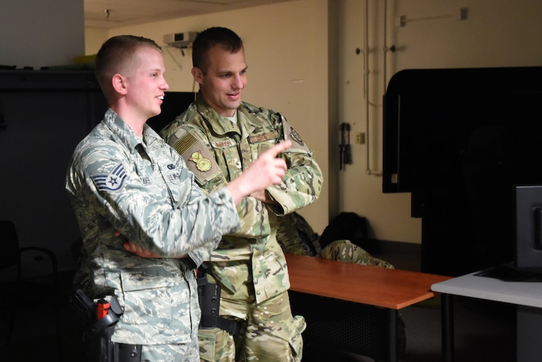 U.S. Air Force Staff Sgt. Kasey Bakker (left), and Senior Airman Kyle Johnson (right), 145th Security Forces Squadron, strategize prior to conducting use of force and tactical situational practice in a Fire Arms Training Simulator simulator June 12, 2019 at the 176th Security Forces Squadron in Anchorage, AK. The 145th Security Forces and 263rd Combat Communications Squadrons with the North Carolina Air National Guard, and the 159th Security Forces Squadron with the Louisiana Air National Guard to Joint Base Elmendorf-Richardson travel to train on various tactical and strategic law enforcement procedures during annual training.