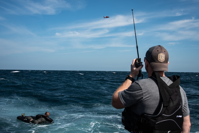 U.S. Air Force Tech. Sgt. David Jones, 20th Operations Support Squadron survival, evasion, resistance and escape noncommissioned officer in charge talks with a U.S. Coast Guard MH-65 Dolphin during a training exercise off the coast of Tybee Island Coast Guard Station, Georgia, June 21.