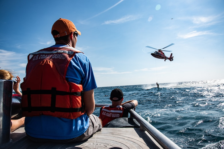 U.S. Airmen and U.S. Coast Guardsmen watch an F-16 pilot be lifted out of the water by a USCG MH-65 Dolphin off the coast of Tybee Island Coast Guard Station, Georgia, June 21. 2019.