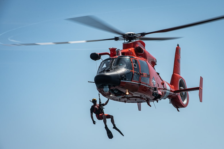 A U.S. Coast Guard (USCG) rescue swimmer hangs of the side of an MH-65 Dolphin off the coast of Tybee Island Coast Guard Station, Georgia, June 21. 2019.